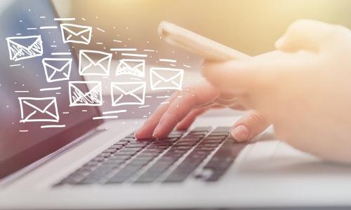 パソコンと携帯を操作してメールを送信している女性