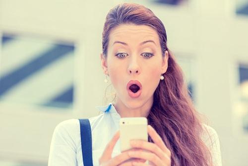 携帯電話を見て驚いている顔をしている女性