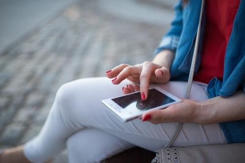 外で携帯を操作している女性