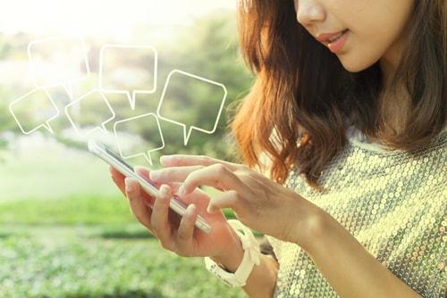 携帯で口コミ・評判・レビューを確認している女性