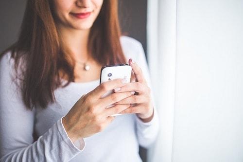 室内で携帯を操作している女性