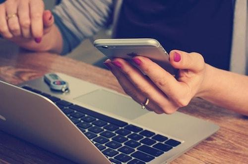 携帯(スマートフォン)とパソコンを使って何かを調べている女性