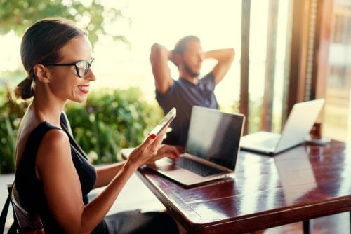 携帯をみながらパソコンを操作している女性とパソコンの前で腕を組んで考え事をしている男性