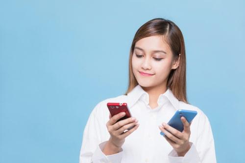 二つの携帯を持って比較している女性