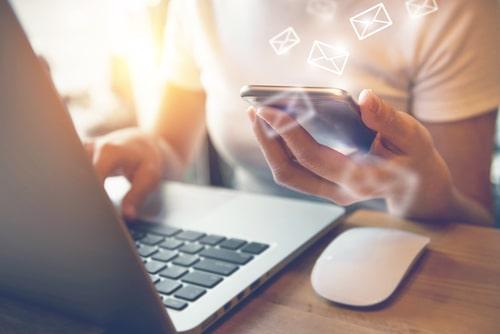 携帯を操作しながらパソコンでメールを確認している女性