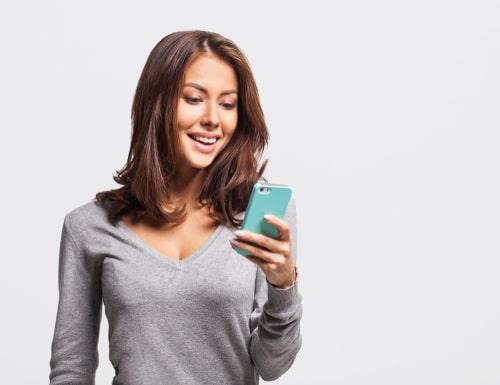 携帯を操作しながら笑顔をこぼしている女性