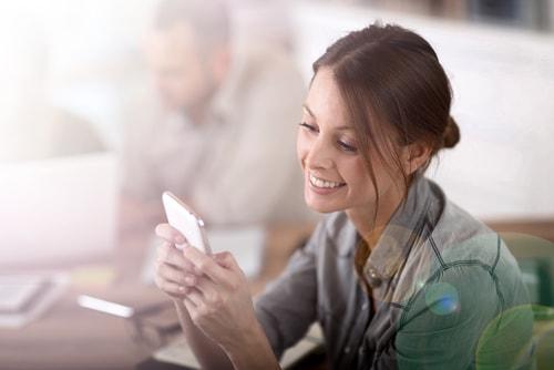 携帯を見ながら嬉しそうな顔をしている女性