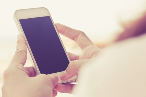女性が携帯電話を操作してメール占いを行おうとしている画像