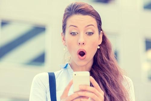 女性が携帯に送られてきたメール鑑定をみて驚いている様子