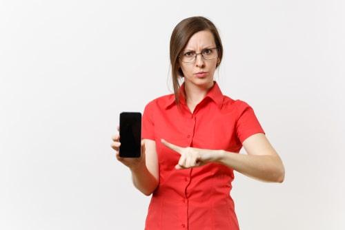 女性が携帯を指差してこちらに何かを訴えかけている様子