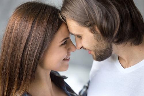 女性と男性がお互いの顔をみて微笑みあっている様子