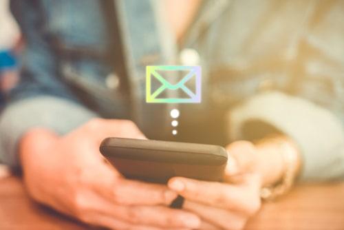 女性がスマートフォンでメールを送信している様子